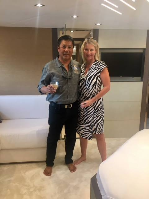 "Local world-renowned ""sea life"" artist, Carey Chen joined us for the event. On a tour of the Monte Carlo MCY, he and his guest stopped for a photo in the Master Stateroom."